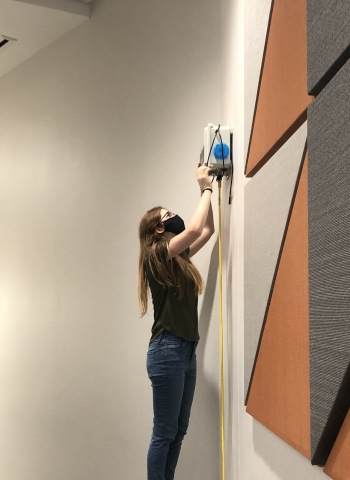 Student inspects air sensor in classroom