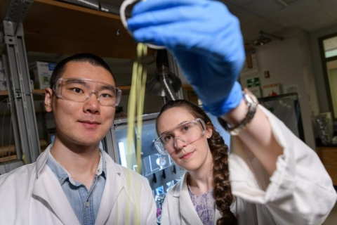 <p>Fengyi Zhang and Emily K. McGuinness, graduate students at Georgia Tech, inspect a hollow fiber membrane that can be used for low-energy chemical separation. (Credit: Rob Felt)</p>