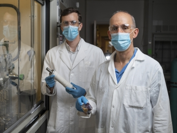 New membrane technology could reduce carbon emissions and energy intensity associated with refining crude oil. Georgia Tech Associate Professor Ryan Lively shows a module containing the new membrane material, while Professor M.G. Finn holds vials containing some of the other polymers used in this study. (Credit: Christopher Moore, Georgia Tech)